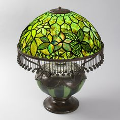 """Woodbine"" Tiffany Lamp  A Tiffany Studios New York glass and bronze ""Woodbine"" table lamp, featuring woodbine leaves in mottled green ""Drapery"" glass against a background of translucent green ""Confetti"" glass. The shade sits atop a blown glass and patinated bronze base. The Byzantine look of this lamp is enhanced a hanging fringe of metal balls surrounding the bottom edge of the shade"