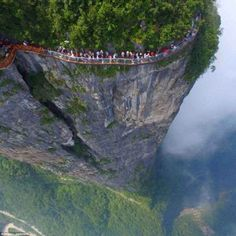 Above the clouds: China's Coiling Dragon Cliff walkway opened in 2016 on Tianmen Mountain in Zhangjiajie - a 330ft-long path along the mountainside which is is just 5ft wide, giving tourists a clear view of the plunging valley beneath