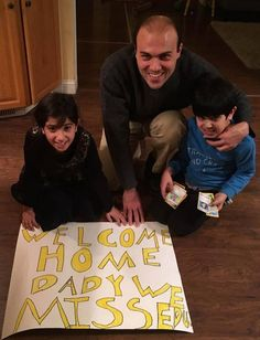 """Rebekka Abedini, 9, and her brother Jacob, 7, show their dad Saeed a """"welcome home"""" poster they made for him following his release from an Iranian prison after three and a half years. Provided by Zybandeh Abedini."""