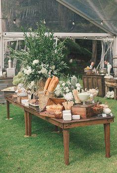 pain de campagne, fromage, et une table de charcuterie décorée avec une pièce maîtresse de la végétation luxuriante et pivoines blanches