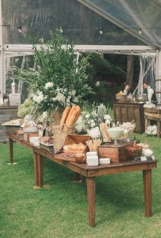 rustic bread, cheese, and charcuterie table decorated with a centerpiece of lush greenery and white peonies