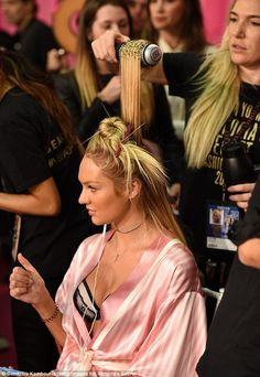 Backstage bustle: Candice - who's fluent in Portuguese - covered her incredible figure up with a pink-striped dressing gown as she had her flaxen locks coiffed