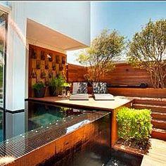 Projeto FL. Espelho d'água revestido com pastilha escura, que combina com o estilo simples e sofisticado da casa. #danielnunespaisagismo