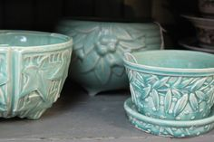 "1940's light blue McCoy flowerpots: ""leaves and berries,"" and ""leaves and hobnail""."