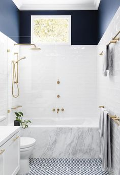 Bathing bliss: This combined bath/shower fits neatly into the end of the space, with a frameless glass screen separating the wet from dry zones, ensuring sight lines travel all the way to the end. A high window offers plenty of sunlight and privacy. Build: GIA Bathrooms & Kitchens | Photography: Martina Gemmola. | 15 bathrooms with clever ideas to steal