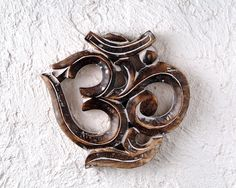 """Wood Om Wall Hanging    """"OM the sound of the universe, that which unites us all into the One.""""   Manifest Peace, Inspiration and Balance with The Chopra Center Wood Om Wall Hanging. Bring grace and beauty to any wall by hanging the sacred symbol of OM. Measures 7.5"""" H x 8""""W."""