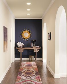 A dark accent wall makes a stunning statement at the end of a hallway. The carefully chosen décor—including an outstanding starburst mirror—creates a lovely vignette that shows how impactful a small space can be. Shown here: Sherwin-Williams Dewberry SW6552 #colorofthemonth #pantone #eclipe #colortrends #homeimprovement #homedecor #accentwall #darkpaintcolors #darkwall #purplehomedecor #darkhomedecor #purpleaccentwall