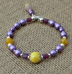 Lavender & Yellow Memory Wire Bracelet $12.00 The+colors+are+just+gorgeous+together!++This+bracelet+is+made+with+opaque+purple+satin+druk+glass+beads,+purple+metallic+6mm+beads,+yellow+dragon+vein+agate+beads,+yellow+ab+focal+bead,+lavender+glass+cube+beads+and+silver+components+with+a+dangle+consisting+of+a+purple+6mm+acrylic+bead+and+a+yel...