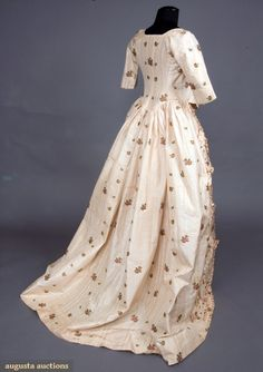 Floral Silk Brocade Robe a L'anglaise with elbow length fitted untrimmed sleeves, waist with front and back rounded point, open front skirt with fly-fringe edged ruched silk applied in zig-zag pattern, skirt knife pleated to bodice back and sides, homespun linen bodice & sleeve lining, (neckline edged with silk ribbon tie, possibly later addition, some staining) excellent.