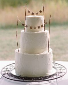 Crafty Cake Garland - This three-tiered lemon cake is topped with a garland made by the groom using Scrabble tiles, twine, sticks, and a drill. Very cute and would be great for a casual, DIY wedding.