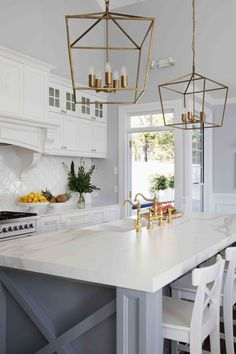 The brass pendant lights add a modern touch to this otherwise classic kitchen. Dining Lighting, Kitchen Pendant Lighting, Kitchen Pendants, Pendant Lights, Kitchen Reno, Kitchen Dining, Kitchen Remodel, Kitchen Ideas, Hamptons Style Homes