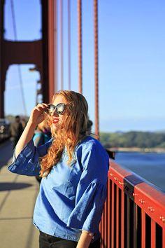 Walking across the Golden Gate Bridge at sunset! San Francisco, California travel tips. Wearing a blue bell sleeve top with Karen Walker sunglasses.