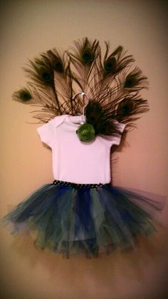 Peacock Tutu Halloween Costume!  How cute is this?!  The tutu and feathers are made on different waist bands, that way when halloween is over your little girl can still utilize the tutu.  Also included in this set is the headband which is clipped to the onesie.  It's peacock feathers with a green flower accent.  Check it out on my etsy site!