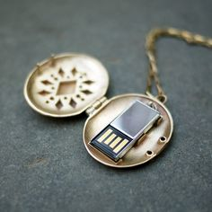 Emily Rothschild. -----    A re-design of a turn-of-the-century mourning locket, this necklace now contains a USB flash drive. Given new life, this locket stores all of your most important photographs and files to be shared or to be kept safe as memories.