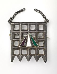 Holloway brooch, designed by Sylvia Pankhurst, 1909. Presented to all British suffragettes after imprisonment, the design was based on the portcullis symbol of the House of Commons, the arrow convict symbol is enamelled in the purple, white and green colours of the suffragettes. Purple stood for dignity, white for purity and green for hope.