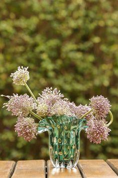 A exótica flor-de-alho tem uma tonalidade lilás encantadora, que ressaltou a beleza do tom esmeralda deste Murano um pouquinho mais alto e robusto. Também uma ótima forma de decorar mesas e cantinhos em diversos ambientes, afinal, as flores são sempre muito bem-vindas! Para uma estação charmosa de chá da tarde, esta composição faz vista e combina com a atmosfera de magia que sempre envolve uma cerimônia simples e tradicional como esta.