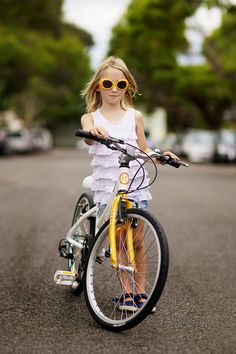 The Cyclist Style | Great photo of a girl on a kids bike - matching yellow sunglasses and yellow ByK makes it the best!