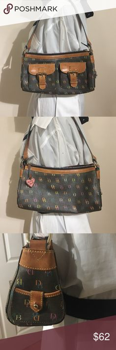 """Adorable little Dooney & Bourke monogrammed bag Adorable little vintage Dooney & Bourke black coated canvas and leather trim monogrammed shoulder bag with silver hardware, front has 2 functional belted pockets, small functional pockets on both ends 11""""W 6""""T 9"""" shoulder strap 4""""D rainbow zippered closure, Dooney &Bourke heart on leather tab zipper pull. Inside lined in blue fabric has 1 zippered pocket and 1 slip pocket, attached keychain with dog leash clip. Dooney & Bourke Bags Shoulder…"""