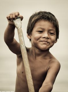 A boy from the Amazon Rainforest of North Brazil paddling his canoe. I like his expression.