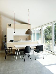 The interior finish consists of three materials: concrete for the heated floors, white plaster covering the outside walls and ceiling, and birch veneer plywood for the interior partitions and kitchen cabinetry. The use of birch plywood was a cost-effective way to include a large expanse of wood finish. The interior doors are faced with the same birch.