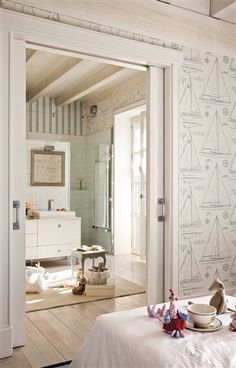 nautical wallpaper, pocket doors, bleached wood, and a view of a contemporary bath