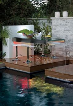 note: ..and why not?  Poolside outdoor dining area or bar seating with an unusual waterfall table  (via Phil Kean Designs)