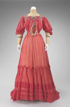 This 1903 Jacques Doucet afternoon dress is a perfect example of couture during this period. The sheer pink fabric, accented with lace and black and pink ribbon trim, is a dress to be displayed at garden parties and the races. Doucet added interest to his work with his use of unusual trims, illustrating his inventiveness and artistic taste.