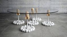 """DESIGN DE PRODUTOS - Para quem gosta de peças inusitadas e divertidas na sua casa, vai adorar a nova criação do designer Mousarris. Se trata da ROCKET COFFEE TABLE, que bem como o nome diz, é uma mesa que possui as pernas em formato de foguetes decolando. Isso mesmo,foguetes! O topo da mesa é de vidro e os foguetes de madeira, assim como a """"fumaça"""" que sai. Os foguetes são cuidadosamente talhados na madeira fazendo com que nos recordemos de nossos brinquedos de crianças."""