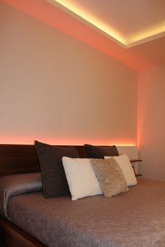 Dormitorio iluminado con tiras de LEDs RGB en cabecero y foseado.
