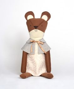 Eleanor the Bear  Handmade in the USA    Soft 100% brushed wool; wool felt for face and tail details. Stuffed with kapok. Comes dressed in fully functional, removable, and interchangeable clothes. Limited run tweed capelet with gold ribbon closure, brocade dress with cotton lining. Faces are hand-embroidered. Made in the USA from locally-sourced materials whenever possible.