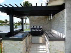 Built-in BBQ Pergola Stacked Stone Outdoor Kitchen by Outdoor Kitchens & Living of Florida.