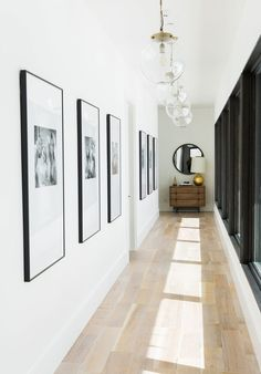 Pendant lights by Arteriors light a hallway, where an RH mirror hangs above a Noir dresser.