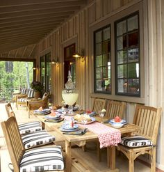 Outdoor furniture sets the scene for front porch dining. Transitional styling -- simple lines and natural teak -- make the dining set at home anywhere, including the primitive exterior of Whisper Creek Cottage.
