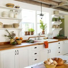White-painted base cabinets give this farmhouse kitchen an elegant simplicity, while open shelves and exposed beams add a sense of loftiness. | Photo: Wendell T. Webber | thisoldhouse.com