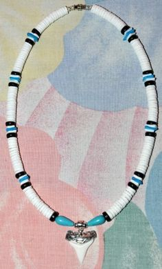 "Native Treasure Custom Shark Tooth Puka Shell Necklace with Sharks Carved in Silver - 18 Inch by Native Treasure. $49.95. This Very Special Native Treasure Puka Shell Necklace is Beautifully Hand-crafted in our Tropical Jewelry Shop by our own Native Island Artisans using 8mm (5/16"")  Hand-Sorted Class 'A' Quality Shells with a 1'' Custom Shark Tooth Pendant! (shape may vary).   .....It is our standard 18"" length and is ideal for Men, Women, Boys and Girls, and..."