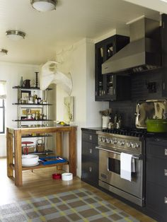 Love the black cabinetry and black tile splash against the stainless steel appliances. Also, check out that antelope head! A-maze-ing! Thom Filicia design.