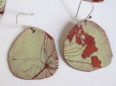 Asymmetrical earrings in organic shapes with a queen annes lace silhouette in pale green enamel. They are made real plants I gathered from my garden and used to block out the sifted glass powder. The lovely reds are the natural copper oxides under a clear glass enamel layer. The ear wire is handmade in sterling silver.  The total length of the earrings: 2 inches (from top of ear wire to bottom of earring) by 1 inch wide.  One of A Kind, no piece is alike.