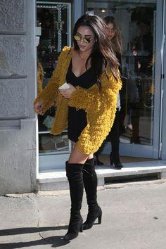 Shay Mitchell lookée avec ses cuissardes For Love & Lemons, et une mini robe noire décolletée.