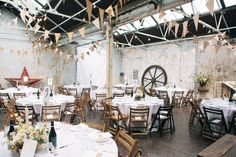 Industrial / Urban reception with brown paper bunting - Image by Lee Robbins Photographic - David Fielden Wedding Dress & Jimmy Choo Shoes for an urban, industrial wedding at MC Motors London City with pastel bridesmaid gowns & Groom in a Vivienne Westwood Suit.
