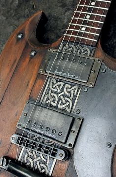 Intricate silver - pewter Celtic type design in unusual place on lovely dark wood electric guitar, below the strings and between the bridge pickups and the saddle. Black pick guard protects and reflects the dark color tones of this beauty. - DdO:) - http://www.pinterest.com/DianaDeeOsborne/instruments-for-joy/ - stringed INSTRUMENTS FOR JOY. Wonderful musical instrument pinned vya AshTheKilljoy.