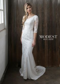Style TR21863 from Mon Cheri Modest is an embroidered tulle over lace and crepe A-line modest bridal gown that has cap sleeves under illusion lace with metallic thread three-quarter sleeves, a modest V-neckline, a concealed back zipper and metallic threaded lace applique that adorns the bodice and cascades straight down the front and back skirt to the hemline and onto the sweep train. Elegant gown for any type of wedding.