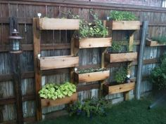 Liven up a plain fence with some cedar planters. -- This will be perfect for our small backyard.