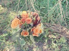 A close-up shot of a Fall bridal bouquet with orange and coral spray roses, orange roses, eucalyptus, baby's breath, lavender, love in the mist, variegated geranium, twigs & greenery.