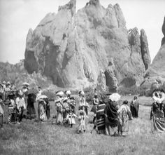 Native American (Ute) men, women, and children participate in a Moon Dance, near The Gateway rock formation at Garden of the Gods, El Paso County, Colorado. Men wear feather headdresses. Women wear blanket shawls. Some women wear hats. Spectators stand nearby, some under umbrellas.  Date 	August 3, 1911