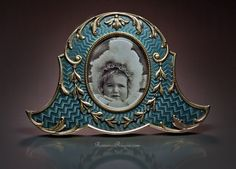 An Antique Faberge Picture Frame    Silver-gilt and translucent gray guilloche enamel miniature picture / photo frame, made in St. Petersburg between 1908 and 1917 by Karl Faberge's workmaster Andrei Gorianov (Gurjanov).    Andrei Gerasimovich Gorianov (Gurjanov)* took over Wilhelm Reimer's workshop at Morskaia St. 11/6  upon Reimer's death in 1898. He worked independently and supplied Faberge primarily with small enameled picture frames and jewelry.