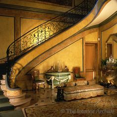 he walls of the entrance hall of the Duke and Duchess of Windor's Paris home are marbleised and the large curved staircase has an ornate wrought-iron balustrade