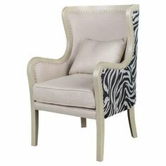 """Hollywood Regency meets safari style in this chic wingback chair, highlighted by nailhead trim and zebra-print upholstery.  Product: ChairConstruction Material: Wood and fabricColor: Cream and blackDimensions: 40"""" H x 25"""" W x 30"""" D"""