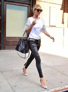 Rosie Huntington- Whiteley steps out in a white shirt with cut-out sleeves, leather pants, a bucket bag, pointed toe printed heels, sunglasses and a belt.
