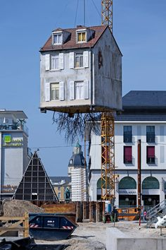 A root system sprouts from the concrete foundations of this house installation that dangles from a crane.
