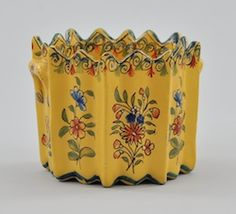 A Petite Quimper Container, French, 19th Century. GLazed pottery container with pinched rim and fluted body, two small decorative handles, overall with French yellow ground and polychrome enamels. Approx. 3 1.4 inches tall X 4 inches diameter